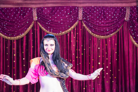 sexy woman standing: Waist Up of Exotic Dark Haired Belly Dancer with Large Snake Around Shoulders, Dancing on Stage with Red Curtain in Background