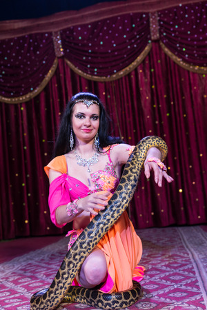 stage costume: Exotic Dark Haired Snake Charmer Dancer Wearing Bright Colored Costume Kneeling on Stage with Large Snake with Red Curtain in Background