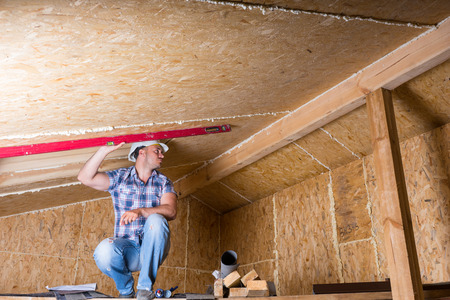 leveling instrument: Male Construction Worker Builder Crouching on Elevated Scaffolding Using Red Level to Measure Grade of Ceiling in Unfinished Home with Exposed Plywood Particle Board Stock Photo