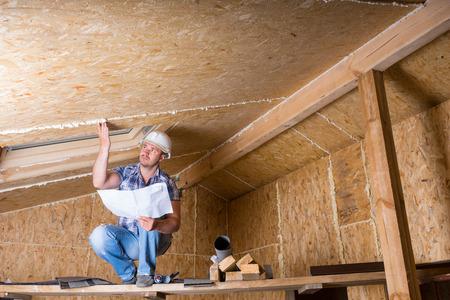 男性建設労働者ビルダーを着て白ハード帽子の上にしゃがみ高架足場と天井の未完成ホーム合板パーティクル ボードの公開に近い読書計画