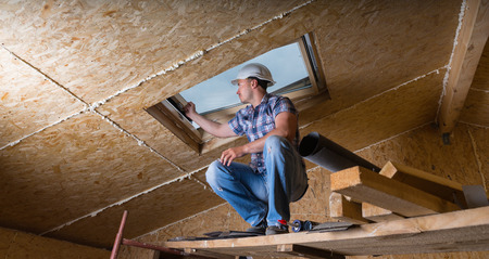 building trade: Low Angle View of Male Construction Worker Builder Crouching on Elevated Scaffolding near Ceiling and Inspecting Frame of Sky Light Window in Unfinished House with Exposed Particle Plywood Board