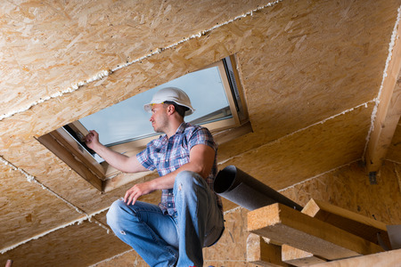 structural engineers: Low Angle View of Male Construction Worker Builder Crouching on Elevated Scaffolding near Ceiling and Inspecting Frame of Sky Light Window in Unfinished House with Exposed Particle Plywood Board