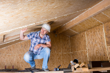 crouching: Male Construction Worker Builder Wearing White Hard Hat Crouching on Elevated Scaffolding near Ceiling in Unfinished House with Exposed Particle Plywood Board