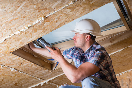 caulking: Male Construction Worker Builder Applying Fresh Caulking to Sky Light in Ceiling of Unfinished Home Stock Photo