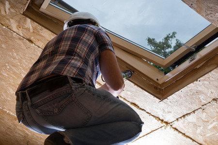 caulking: Low Angle View of Male Construction Worker Builder Applying Fresh Caulking to Sky Light in Ceiling of Unfinished Home