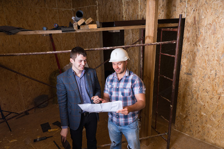 unfinished building: High Angle View of Young Male Architect and Construction Worker Foreman Inspecting Building Plans Together Inside Unfinished Building Stock Photo