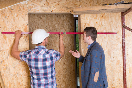 overseer: Builder and Architect Inspecting Construction of Door Frame with Level Inside Unfinished Home with Exposed Particle Plywood Boards Stock Photo