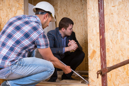ensuring: Builder and Architect Working Together and Inspecting Measurement of New Home Doorway Inside Building Construction Site, Ensuring Accuracy and Quality Stock Photo