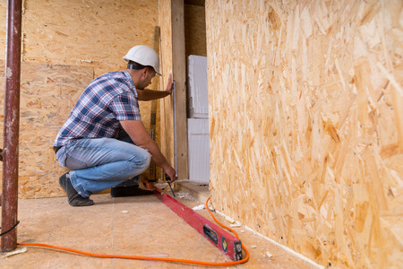 Male Construction Worker Builder Wearing White Hard Hat Measuring Door Frame with Tape Measure Inside Unfinished Home with Exposed Particle Plywood Boards Stok Fotoğraf