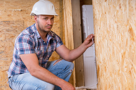overseer: Male Construction Worker Builder Wearing White Hard Hat Measuring Door Frame with Tape Measure Inside Unfinished Home with Exposed Particle Plywood Boards Stock Photo