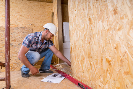 structural engineers: Male Construction Worker Builder Wearing White Hard Hat Measuring Door Frame with Tape Measure Inside Unfinished Home with Exposed Particle Plywood Boards Stock Photo