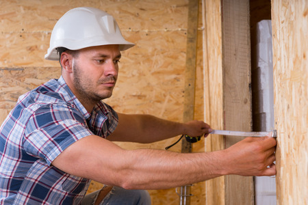 width: Construction Worker Builder Wearing White Hard Hat Measuring Width of Door Frame with Measuring Tape in Unfinished Home