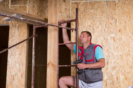 qualified worker: Male Construction Worker Builder Holding Cordless Drill Climbing Up Ladder of Scaffolding Inside Unfinished Home with Exposed Particle Plywood Boards Frame