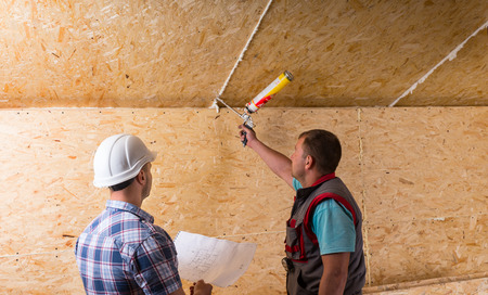 caulking: Construction Site Foreman Wearing White Hard Hat Holding Plans and Observing Worker Applying Caulking to Unfinished Wood Ceiling