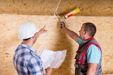 caulk: Foreman Wearing White Hard Hat and Holding Building Plans Instructing Worker How to Apply Caulk to Seam in Unfinished Wood Ceiling in New Home