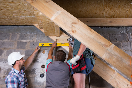 structural engineers: Team of Construction Workers Building Wooden Staircase Frame in Unfinished Basement of New Home, Checking Levels for Accuracy and Quality Control