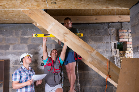 leveling instrument: Team of Construction Workers Building Wooden Staircase Frame in Unfinished Basement of New Home, Checking Levels for Accuracy and Quality Control