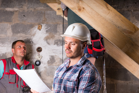leveling instrument: Construction Site Foreman Wearing White Hard Hat and Holding Building Plans in front of Team of Workers Building Wooden Staircase in Unfinished Basement of New Home Stock Photo