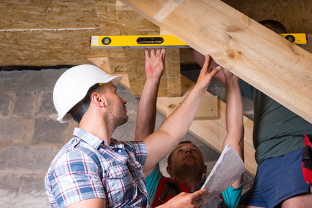 accuracy: Team of Construction Workers Building Wooden Staircase, Checking Levels for Accuracy and Quality Control in Unfinished Basement of New Home Stock Photo