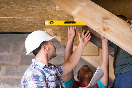 leveling instrument: Team of Construction Workers Building Wooden Staircase, Checking Levels for Accuracy and Quality Control in Unfinished Basement of New Home Stock Photo