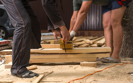 wearing sandals: Two Unrecognizable Men Wearing Sandals Cutting Wood Planks on Informal Construction Site of New Home Stock Photo