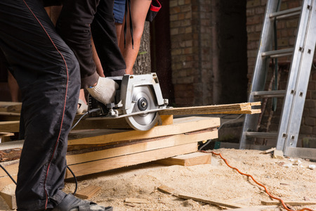 Man Using Hand Held Power Saw to Cut Planks of Wood for Home Construction Leaving Piles of Saw Dust on Floor photo