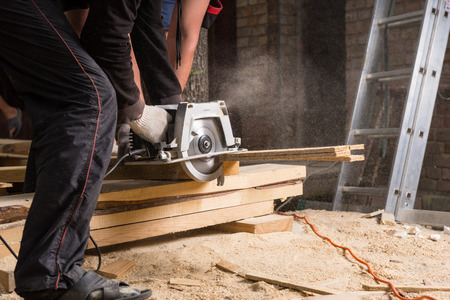 power: Close Up of Two Men Using Hand Held Power Saw to Cut Planks of Wood for Home Construction Leaving Piles of Saw Dust on Floor Stock Photo