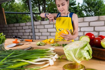 médula: Chica joven que limpia un pimiento sacando la médula con un cuchillo mientras ella se encuentra en una mesa de la preparación de las verduras frescas Foto de archivo