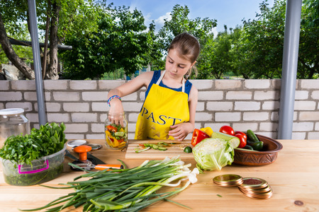 home grown: Attractive young girl standing at on outdoor table in the garden bottling an assortment of fresh home grown vegetables in glass jars