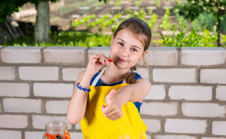 nibbling: Portrait of Smiling Young Girl Nibbling on Fresh Pepper and Giving Thumbs Up to Camera Stock Photo