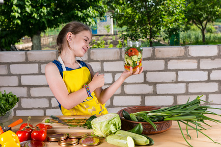laden: Young girl smiling at her jar of fresh vegetables that she has just finished bottling as she stands at a table laden with fresh veggies Stock Photo