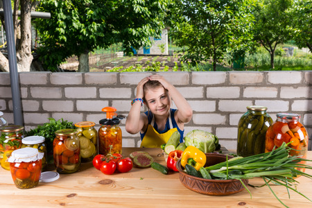 disinterested: Young Girl Looking Tired and Holding Head with Hands, Sitting at Table Surrounded by Fresh Vegetables and Jars of Pickled Preserves Outdoors in Garden Stock Photo