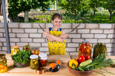 laden: Happy young cook brandishing two kitchen knives above a table laden with freshly bottled vegetables in glass jars Stock Photo