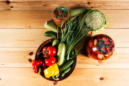 country lifestyle: Bottling fresh vegetables for storage with assorted fresh veggies on a wooden table with two glass jarsof homemade preserves in a country lifestyle concept