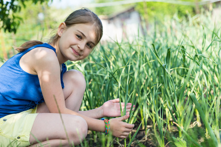bending down: Smiling young girl checking onion plants in a vegetable garden on a smallholding bending down and looking at the camera with a friendly grin Stock Photo