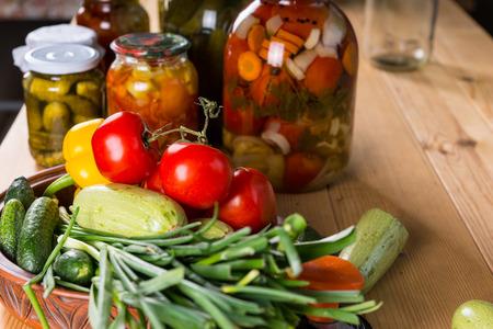 bounty: Todavía vida de la Bounty de verduras frescas y frascos de encurtidos en mesa de madera
