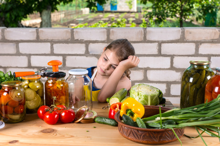 dejected: Dejected young girl bottling vegetables sitting at an outdoor table with her head on her hands staring at a large assortment of fresh veggies and glass jars Stock Photo