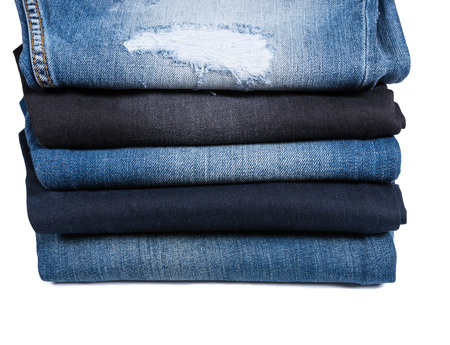 worn jeans: Side Profile View of Different Types of Blue Jeans Folded and Stacked on White Background, Five Denim Jeans of Varying Color Washes and Styles
