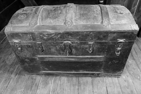 treasure trove: Black and White Image of Old Dusty Antique Treasure Chest with Rusty Iron Accents and Key in Lock on Deck of Sailing Ship