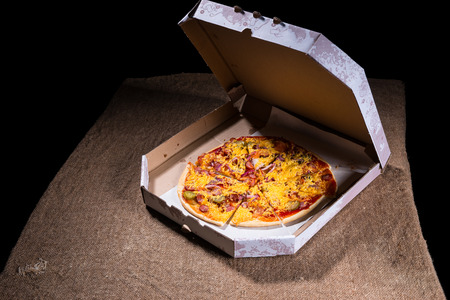 open topped: High Angle View of Artisan Pizza Topped with Variety of Toppings and Cheese in Carboard Take Out Box with Open Lid on Table Surface with Copy Space