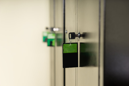 closed lock: Key and attached label in a lock on a metal cabinet viewed from the side with a green tag and copyspace on the label in a safety and security concept Stock Photo