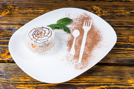 High Angle View of Decadent Dessert with Spider Web Design on White Plate with Mint Leaf Garnish and Utensil Outlines Dusted in Chocolate Shavings