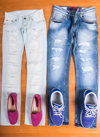 coordinating: High Angle View of His and Hers Distressed and Torn Blue Jeans Laid Out Flat on Wooden Surface with Coordinating Shoes - Pink Loafers and Purple Sneakers