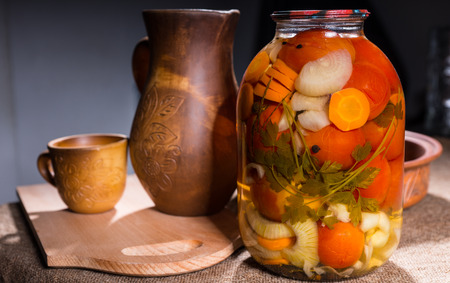 preserves: Jar of Pickled Vegetable Preserves on Table Surface Next to Carved Wooden Handicrafts - Wood Pitcher, Cup, Bowl and Wooden Cutting Board Stock Photo