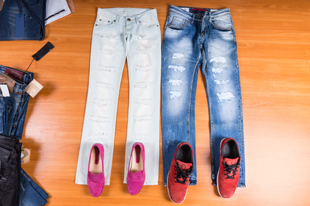 coordinating: High Angle View of His and Hers Distressed and Torn Blue Jeans Laid Out Flat on Wooden Surface with Coordinating Shoes - Stylish Pink Loafers and Red Sneakers Stock Photo