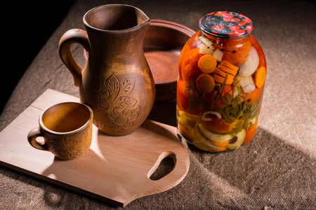 preserves: Jar of Pickled Vegetable Preserves on Rustic Burlap Covered Table Surface Next to Carved Wooden Handicrafts - Wood Pitcher, Cup, Bowl and Wooden Cutting Board
