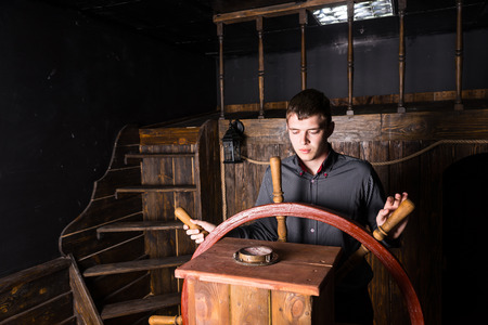 wheelhouse: Concept Image of Young Ambitious Business Man Taking the Helm and Steering Large Antique Wooden Sailing Ship, Looking Down at Compass to Check Direction