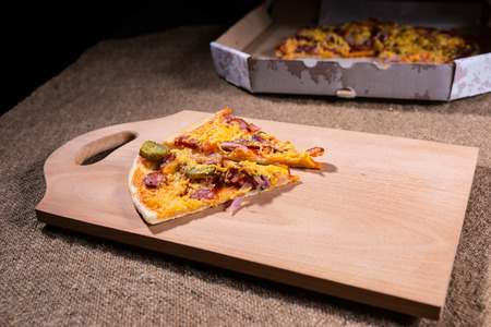 out of the box: Slices of Artisinal Pizza on Wooden Cutting Board with Cardboard Take Out Box in Background on Burlap Covered Table Stock Photo