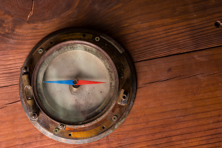 navigating: Old brass ships compass for navigating the globe in a sailing ship on a wooden cabinet with copyspace