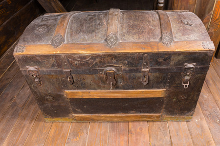 treasure: Looking Down at Old Dusty Antique Treasure Chest with Rusty Iron Accents and Key in Lock on Deck of Sailing Ship Stock Photo